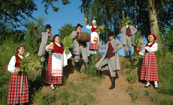 Traditionally dressed Latvians with beer cups and flowers.